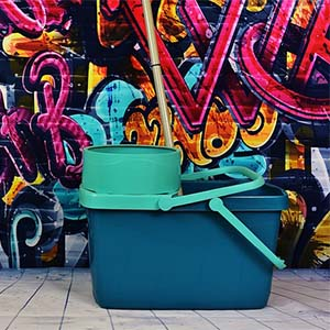 A Graffiti covered wall with a bucket and mop infront - H&W do graffiti removal