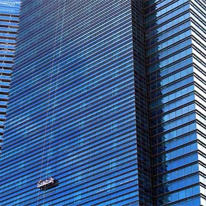 Office Cleaning Services - A Large office building and window cleaners using a platform to clean each window.