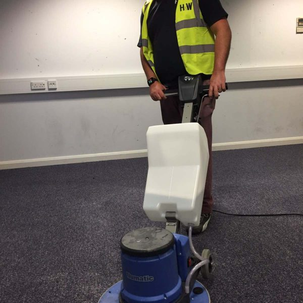 Retail Cleaning Services - Retail cleaning of a carpet by H&W Staff who is wearing a high vis jtop